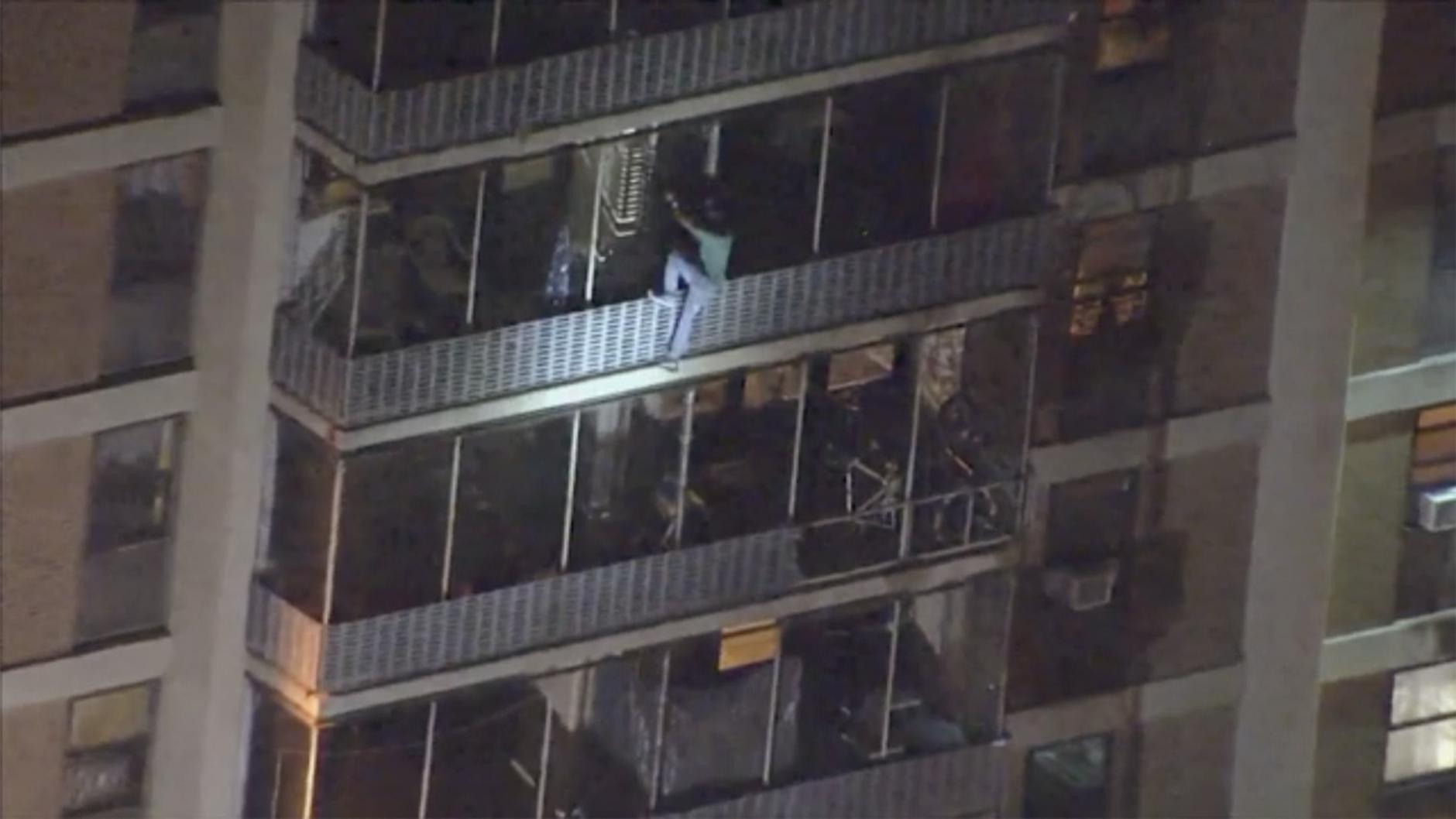 Mann klettert Fassade runter High Rise Feuer
