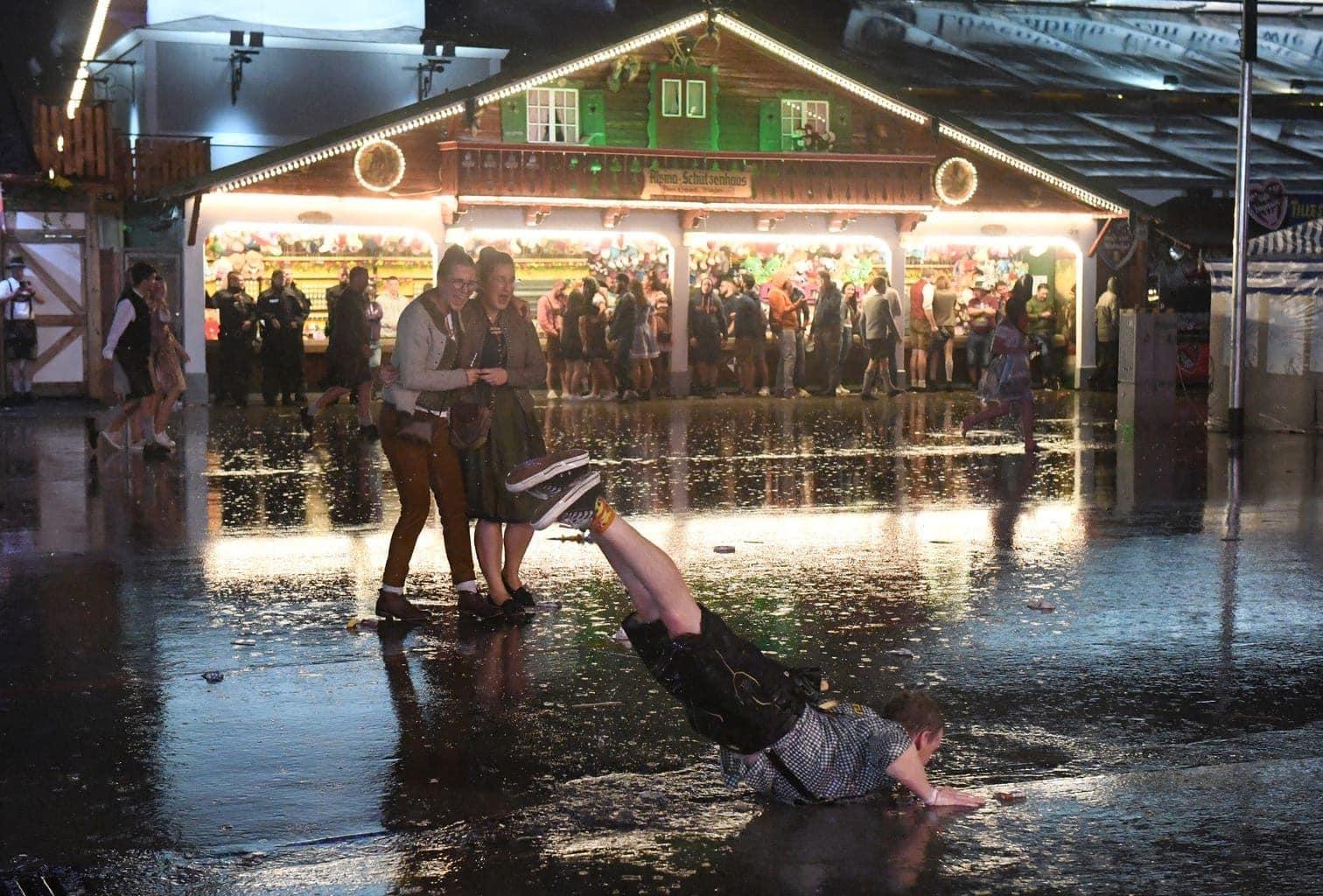 <p>Spektauklär: Dieser Wiesn-Besucher verwechselt Regenwasser mit Eis und wähnt sich auf einer Rodelbahn.</p> Foto: dpa