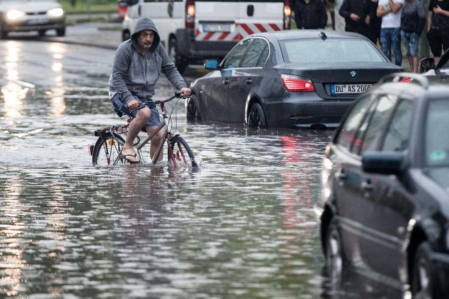 <p>In Duisburg kämpft sich ein Radfahrer durch die meterhohe Flut.</p> Foto: dpa