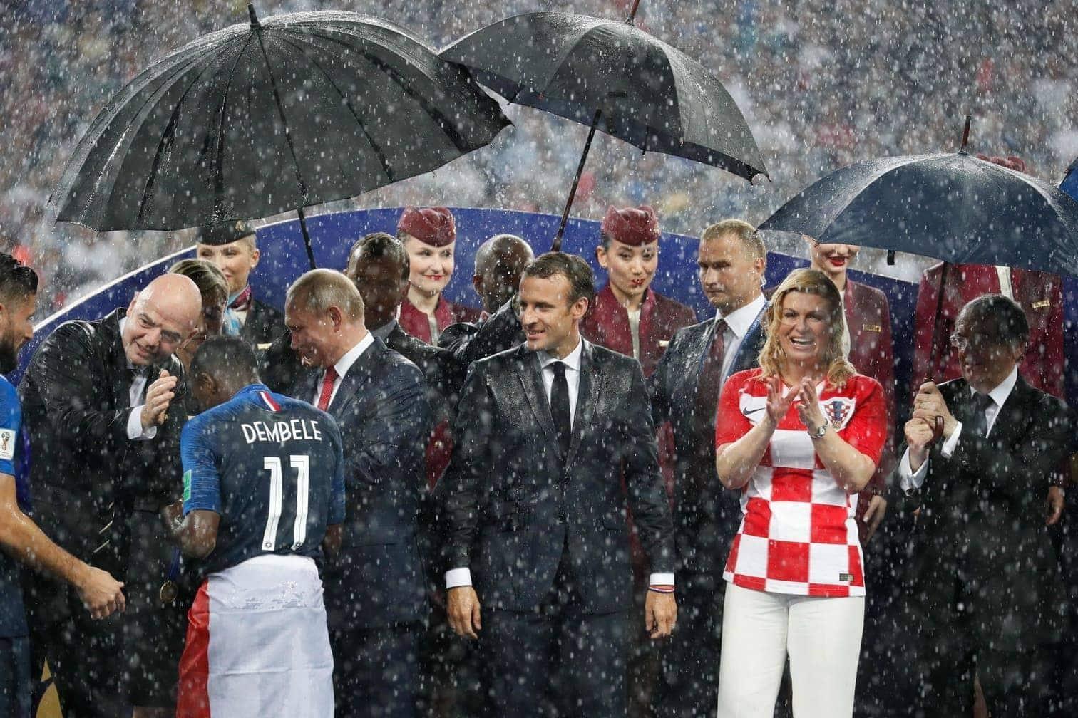 <p>Das scheint für alle Beteiligten ganz normal zu sein. Selbst der Fifa-Chef Gianni Infantino (links) winkt lässig im Regen ab. Macron jubelt über den französischen Triumph &ndash; der Regen scheint ihm komplett egal zu sein.</p> Foto: dpa