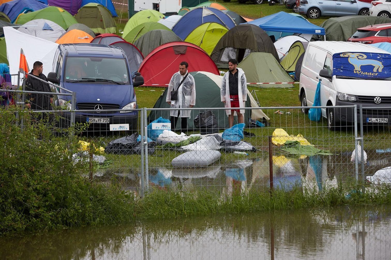 <p>Ein Teich hat sich nach einem kräftigen Gewitterregen auf dem Campinggelände der Musikfestivals gebildet.</p> Foto: dpa